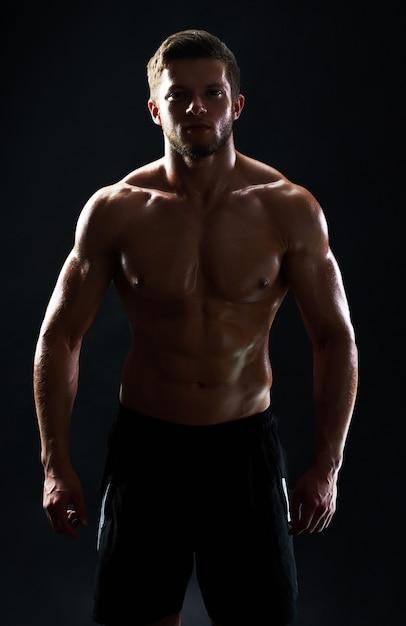 Jonge gespierde fit sportman poseren shirtless op zwarte pagina Gratis Foto