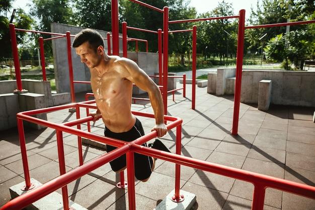 Jonge gespierde shirtless blanke man doet pull-ups op horizontale balk op speelplaats in zonnige zomerdag Gratis Foto