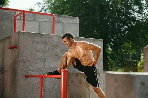 Jonge gespierde shirtless blanke man doet rekoefeningen op de speelplaats in zonnige zomerdag Gratis Foto