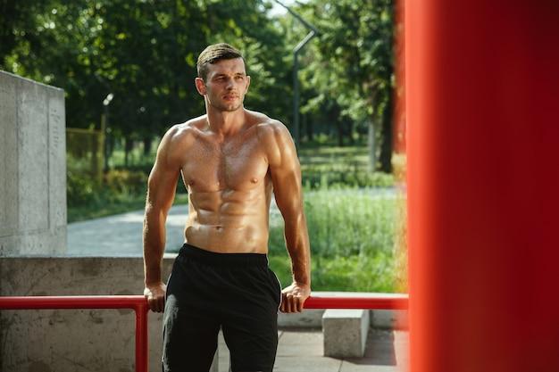 Jonge gespierde shirtless blanke man tijdens zijn training op horizontale balken op de speelplaats in zonnige zomerdag Gratis Foto