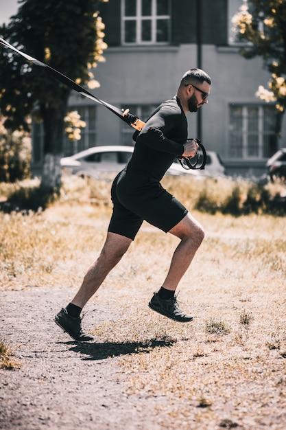 Jonge gespierde sportman training met trx weerstand banden in het park Premium Foto