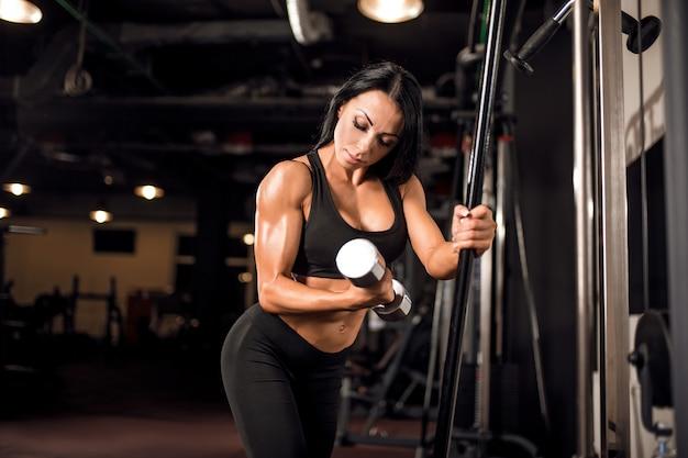 Jonge gespierde vrouw training in de sportschool Premium Foto