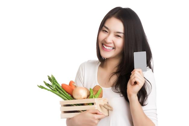 Jonge gezonde aziatische vrouw met verse biologische groente in de mand, de creditcard van de handholding. Premium Foto