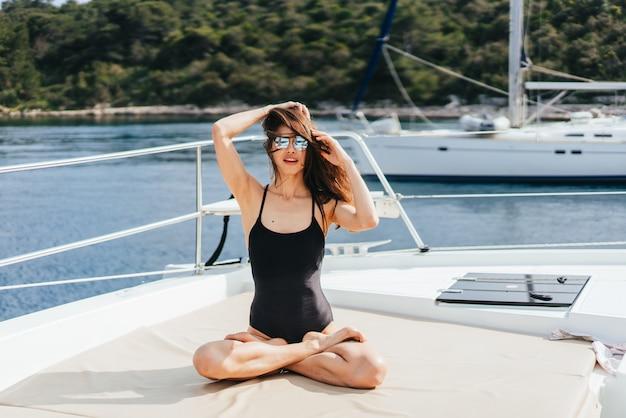 Jonge gezonde en kalme vrouw die yoga op varende jachtboot doen in overzees bij eiland Gratis Foto