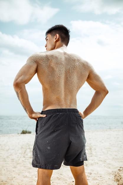 Jonge gezonde man atleet doet squats op het strand Gratis Foto