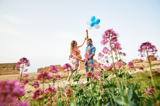 Jonge gezonde schoonheids zwangere vrouw met haar echtgenoot en ballons in openlucht Premium Foto