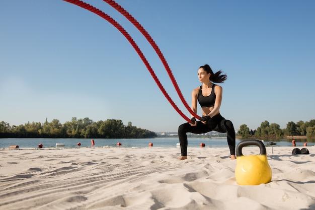 Jonge gezonde vrouw die oefening met de touwen doet op het strand. Gratis Foto