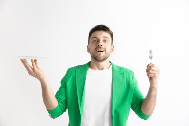 Jonge glimlachende aantrekkelijke kaukasische kerel die lege die schotel en vork houdt die op grijs wordt geïsoleerd. Gratis Foto