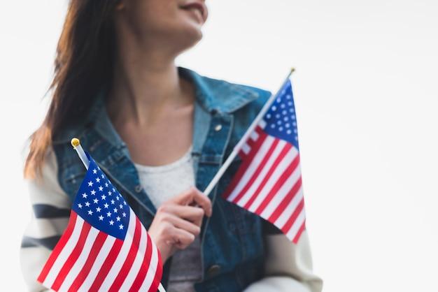 Jonge glimlachende dame die amerikaanse vlaggen houdt Gratis Foto