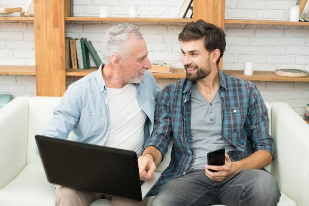 Jonge glimlachende kerel met smartphone die op monitor van laptop op benen van de oude mens op bank richten Gratis Foto