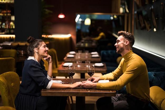 Jonge glimlachende man en de vrolijke handen van de vrouwenholding bij lijst met glazen wijn in restaurant Gratis Foto
