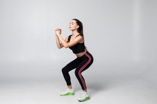 Jonge glimlachende sportvrouw die hurkzit op grijze muur doen Gratis Foto