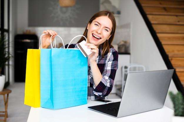 Jonge glimlachende vrouw die het winkelen zakken toont Gratis Foto