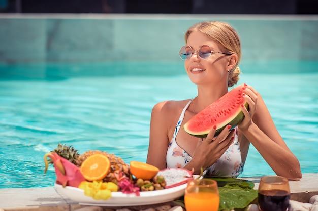 Jonge glimlachende vrouw die in de blauwe pool drijft en verse watermeloen in haar handen houdt Premium Foto