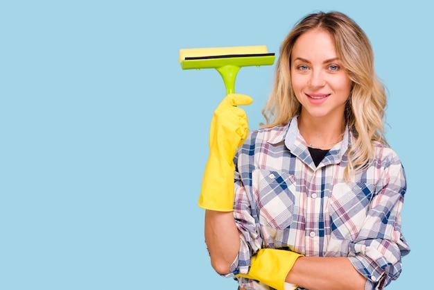 Jonge glimlachende vrouw die plastic wisser houden bekijkend camera tegen blauwe achtergrond Gratis Foto