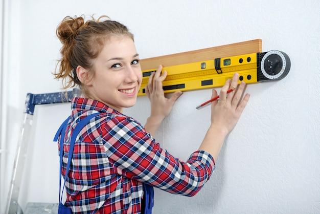 Jonge glimlachende vrouw die waterpas gebruikt Premium Foto