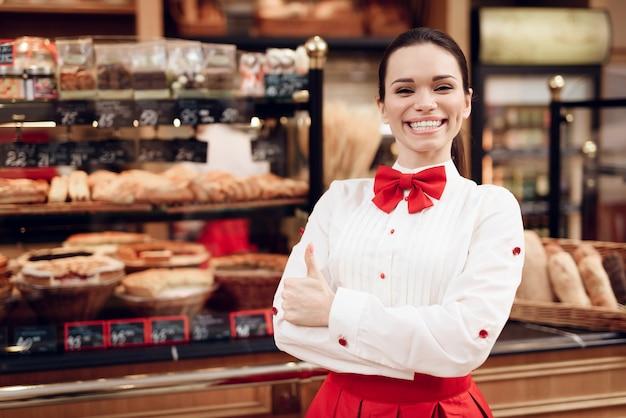 Jonge glimlachende vrouw die zich in moderne bakkerij bevindt. Premium Foto