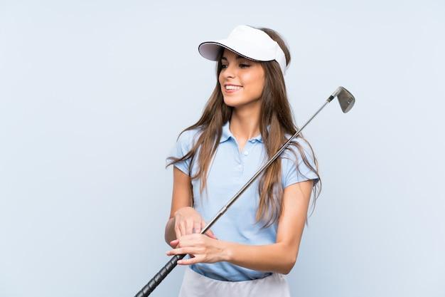 Jonge golfspelervrouw over geïsoleerde blauwe muur die veel glimlacht Premium Foto