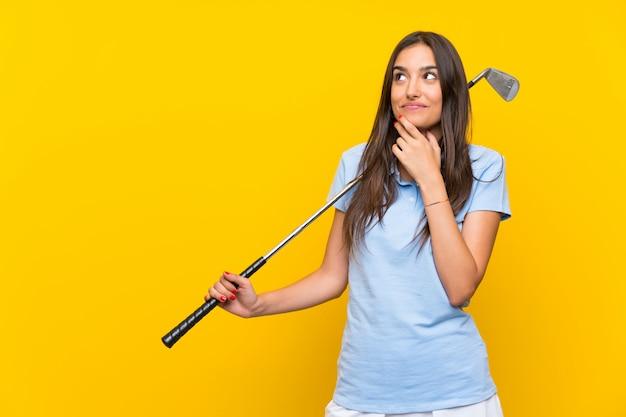 Jonge golfspelervrouw over geïsoleerde gele muur die een idee denkt Premium Foto