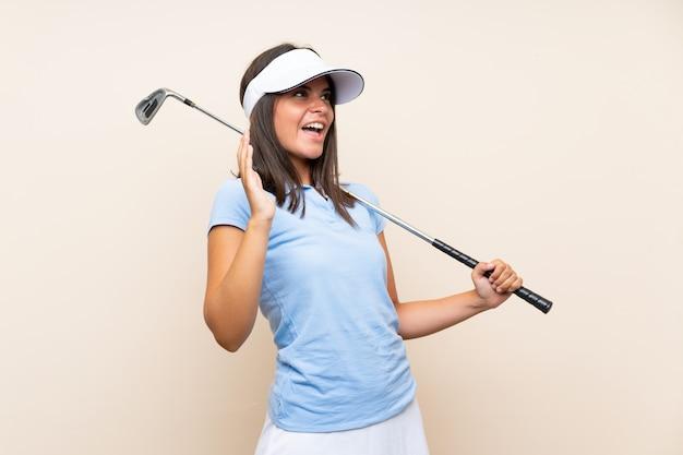 Jonge golfspelervrouw over geïsoleerde muur met verrassingsgelaatsuitdrukking Premium Foto