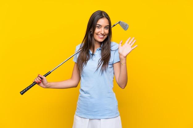 Jonge golfspelervrouw over het geïsoleerde gele muur groeten met hand met gelukkige uitdrukking Premium Foto
