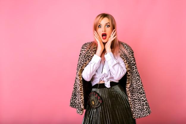 Jonge grappig verrast geschokt vrouw die zich voordeed op roze achtergrond, het dragen van een wit overhemd en luipaardjas, krachtige emoties. Gratis Foto