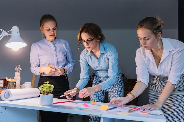 Jonge groep creatieve onderneemster die aan bedrijfsproject op het kantoor werken Gratis Foto