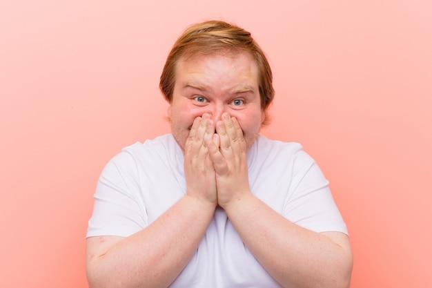 Jonge groot formaat man op zoek gelukkig, vrolijk, gelukkig en verrast bedekkende mond met beide handen over roze muur Premium Foto