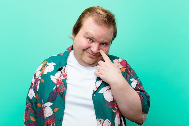 Jonge grote man die je in de gaten houdt, niet vertrouwt, alert en waakzaam blijft en waakt over de blauwe muur Premium Foto
