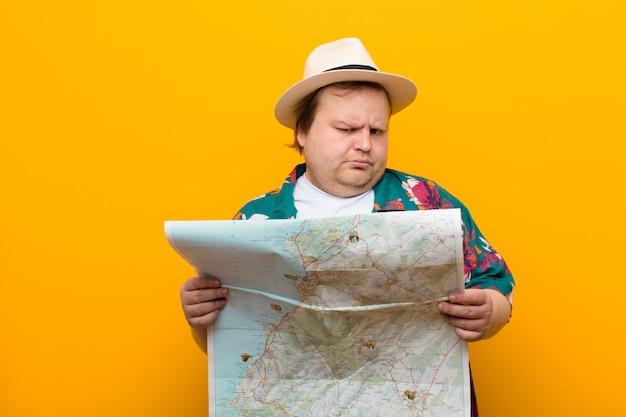 Jonge grote man met een kaart tegen een vlakke muur Premium Foto