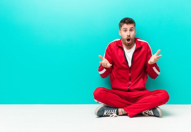 Jonge handosme man voelt zich extreem geschokt en verrast, angstig en in paniek, met een gestresste en gruwelijke blik tegen een vlakke kleurenmuur Premium Foto