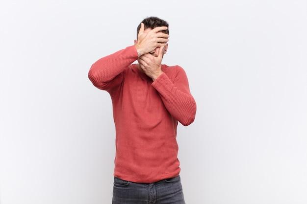 Jonge handosmeman die gezicht behandelt met beide handen die nee zeggen tegen de camera! afbeeldingen weigeren of foto's verbieden over een kleurenmuur Premium Foto