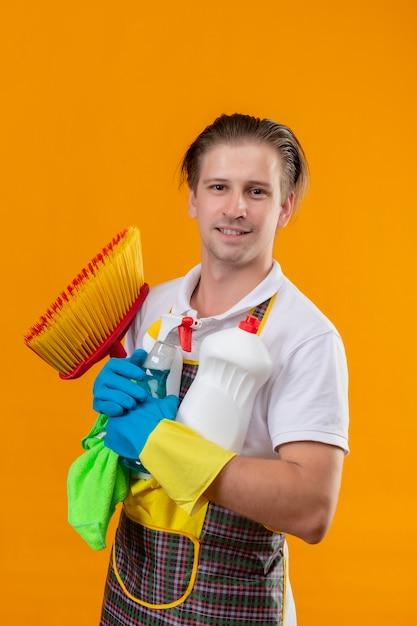 Jonge hansdome-mens die schort en rubberhandschoenen draagt die schoonmakende hulpmiddelen houden Gratis Foto
