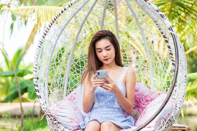 Jonge het gebruikssmartphone van de vrouwenzitting in witte schommeling Gratis Foto