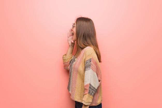 Jonge hippievrouw op roze muur het fluisteren roddel ondertoon Premium Foto
