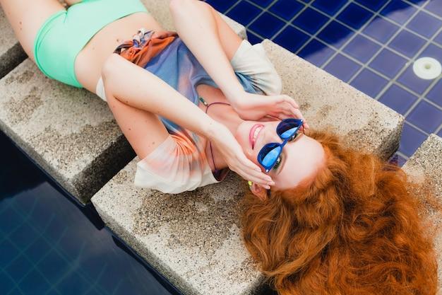 Jonge hipster gember slanke vrouw liggend bij zwembad, uitzicht van bovenaf, rood haar kleurrijk, blauwe zonnebril, sportstijl, sproeten, moedervlekken, ontspannen, gelukkig, speels, coole outfit, glimlachen, sensueel Gratis Foto