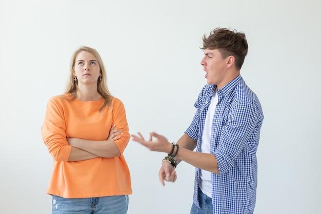 Jonge hipster kerel roept zijn handen omhoog naar zijn geliefde meisje op een witte achtergrond. concept van Premium Foto