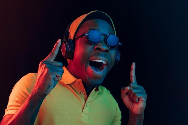 Jonge hipster man luisteren muziek met koptelefoon in zwarte studio met neonlichten. Gratis Foto