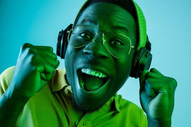 Jonge hipster man luisteren muziek met koptelefoon op blauwe studio met neonlichten. emotionele uitdrukking Gratis Foto