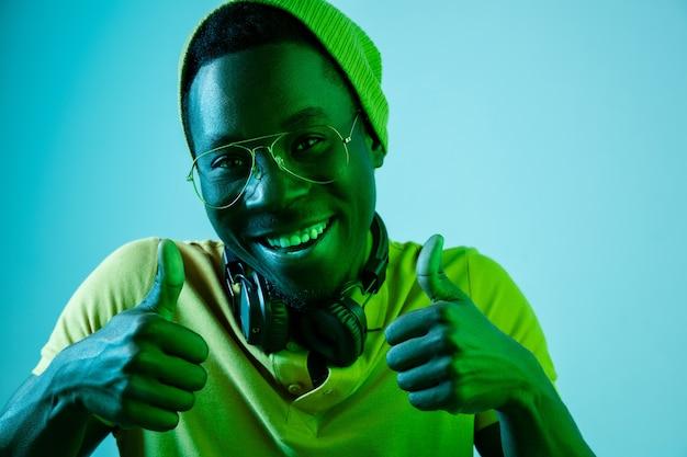 Jonge hipster man luisteren muziek met koptelefoon op blauwe studio met neonlichten. Gratis Foto