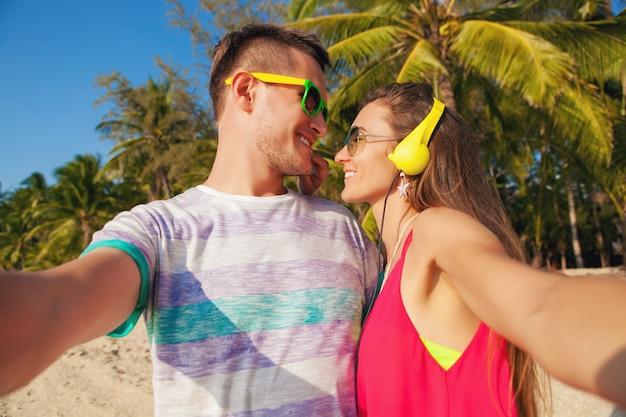 Jonge hipster mooie paar verliefd selfie foto maken op tropisch strand, zomervakantie, gelukkig samen, huwelijksreis, kleurrijke stijl, zonnebril, koptelefoon, glimlachen, gelukkig, plezier hebben, positief Gratis Foto