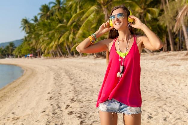 Jonge hipster mooie vrouw, tropisch strand, vakantie, kleurrijk, zomertrendstijl, zonnebril, koptelefoon, luisteren naar muziek, palmbomen achtergrond, glimlachen gelukkig, pret, details, close-up portret Gratis Foto