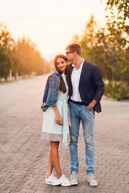 Jonge hipster paar verliefd buiten. prachtig sensueel portret van jonge stijlvolle mode paar poseren in de zomer zonsondergang. vrij jong meisje in jeansjasje en haar knappe vriend die lopen. Gratis Foto
