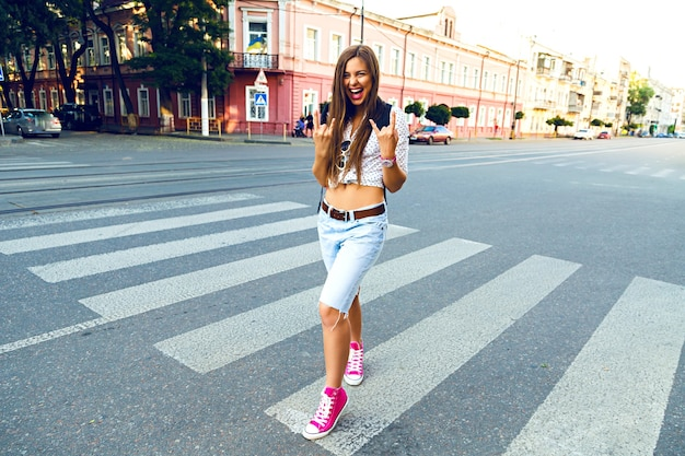 Jonge hipster vrouw gek en plezier hebben in het centrum van europa, wandelen en alleen reizen, vreugde, emoties, stijlvolle casual kleding en rugzak, zonnige heldere kleuren Gratis Foto