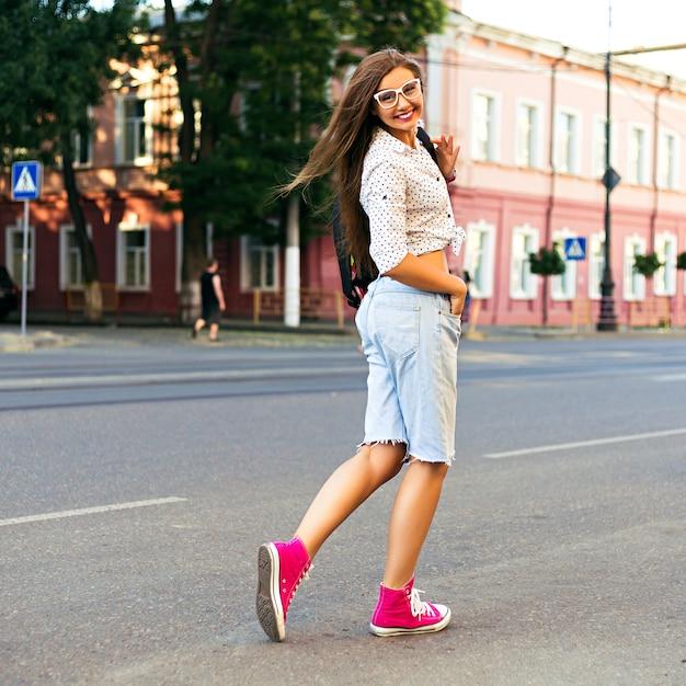 Jonge hipster vrouw gek en plezier hebben in het centrum van europa, wandelen en alleen reizen, vreugde, emoties, stijlvolle casual kleding en rugzak, zonnige warme heldere kleuren Gratis Foto