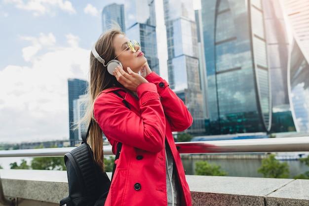 Jonge hipster vrouw in roze jas, jeans in straat met rugzak luisteren naar muziek op koptelefoon, zonnebril dragen Gratis Foto