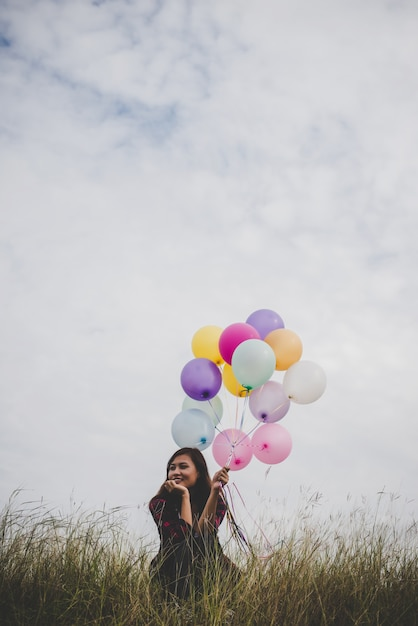 Jonge hipster vrouw zitten met kleurrijke ballonnen in het veld, blauwe hemel achtergrond. Premium Foto