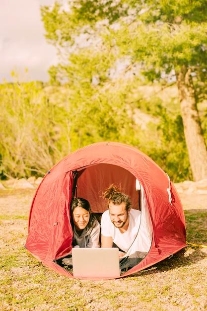 Jonge hipsters die in tent met laptop ontspannen Gratis Foto