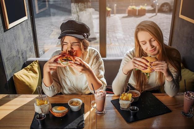 Jonge hongerige vrouwen zitten binnen aan tafel. ze eten hamburgers. modellen eten graag. zij vinden het leuk. Premium Foto