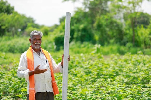 Jonge indiase boer bedrijf pijp op katoen veld. Premium Foto